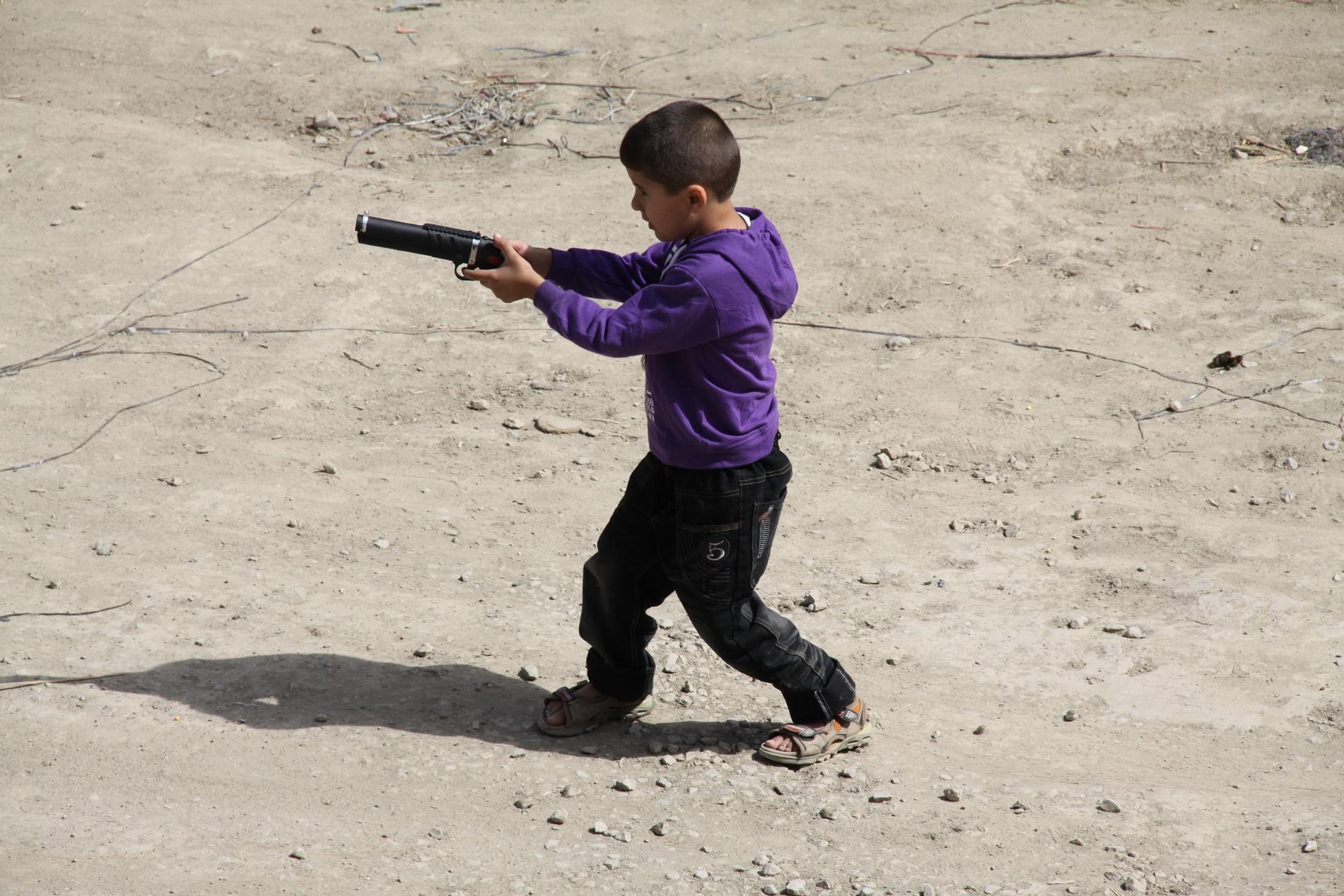 Jovem brinca com um arma de brinquedo no Afeganistão. Acabar com a banalização da violência é dos grandes desafios dos Objetivos do Desenvolvimento Sustentável (ODS)