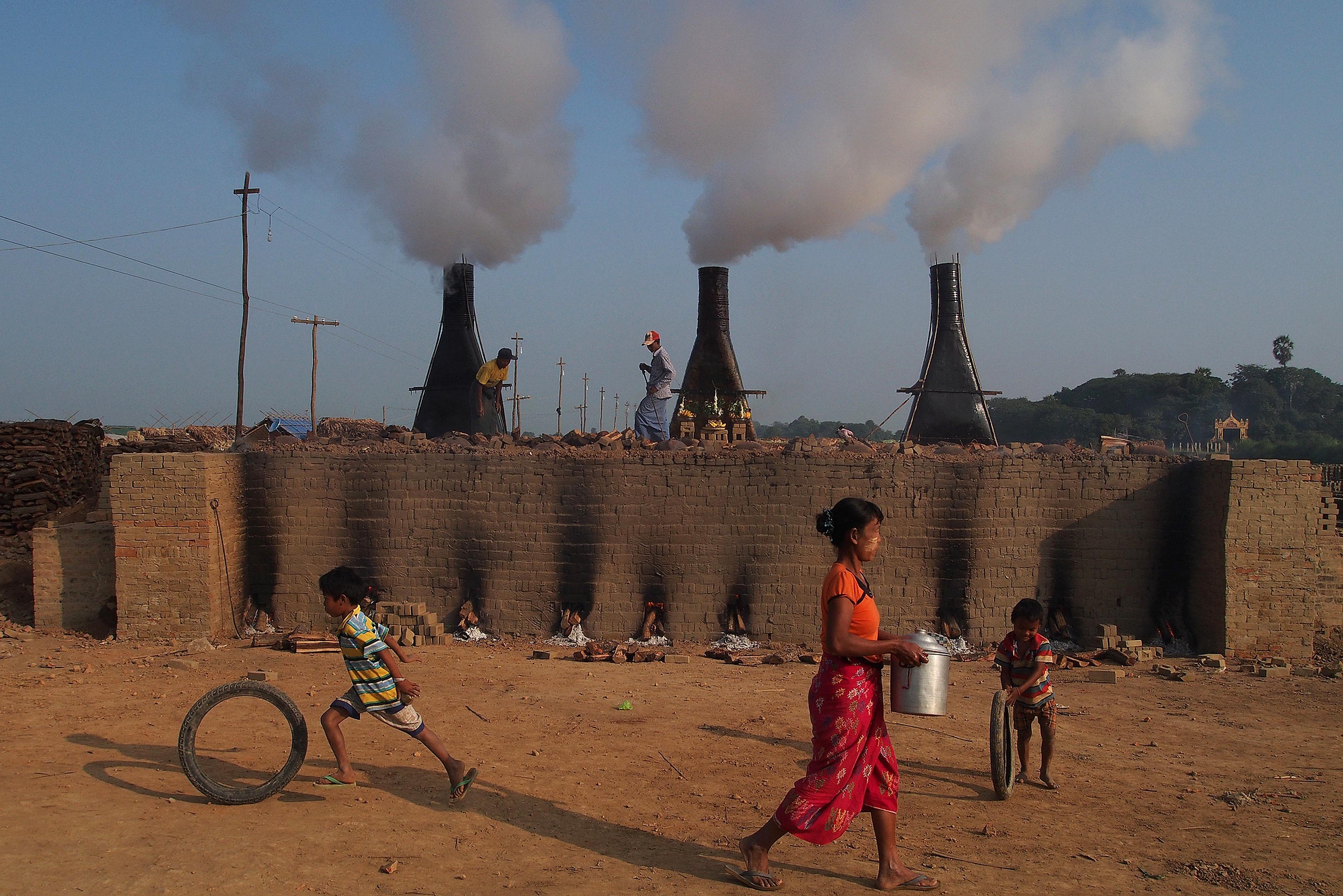 Crianças acompanhadas da mãe brincam em frente uma carvoaria em Miamar
