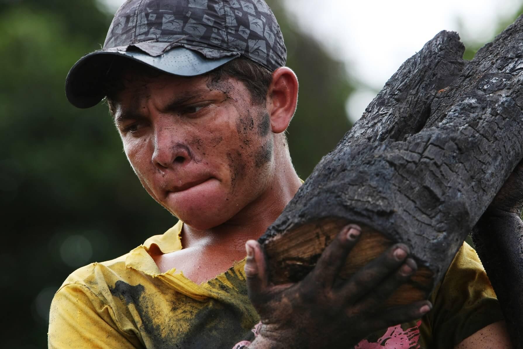 Jovem carvoeiro carrega tronco num dos muitos fornos clandestinos da Região Amazônica. Foto Antonio Scorza