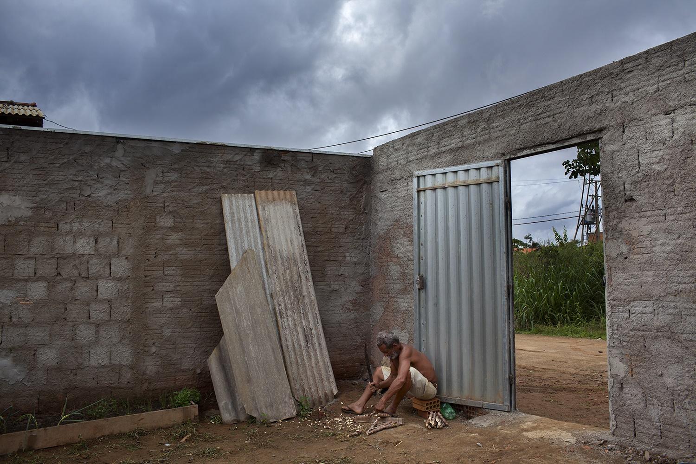 João Pereira da Silva, 64 anos, pescador, prepara mudas de mandioca para plantar num terreno ao lado da nova casa