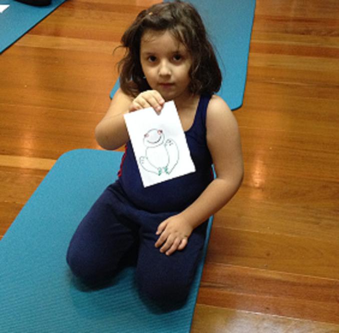 Luiza mostra o desenho do sapo, umas das posições que precisa seguir durante as aulas