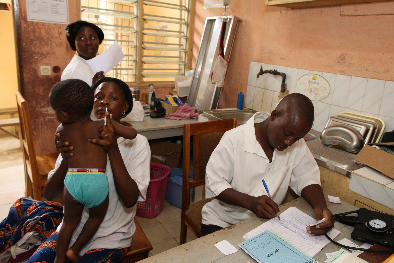 Criança com Aids sendo atendida em centro médico no Togo