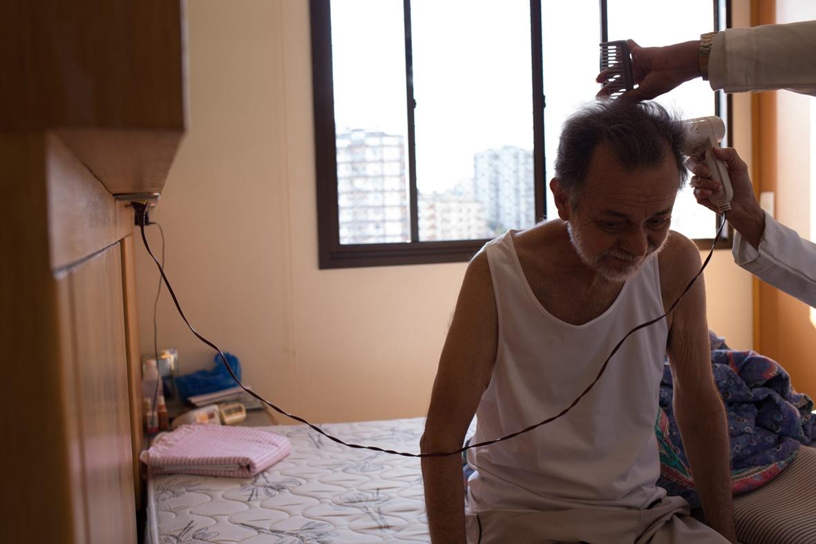 Paulo secando seu cabelo com a ajuda da enfermeira J. antes de ir ao Hospital são Francisco de Assis para uma consulta médica
