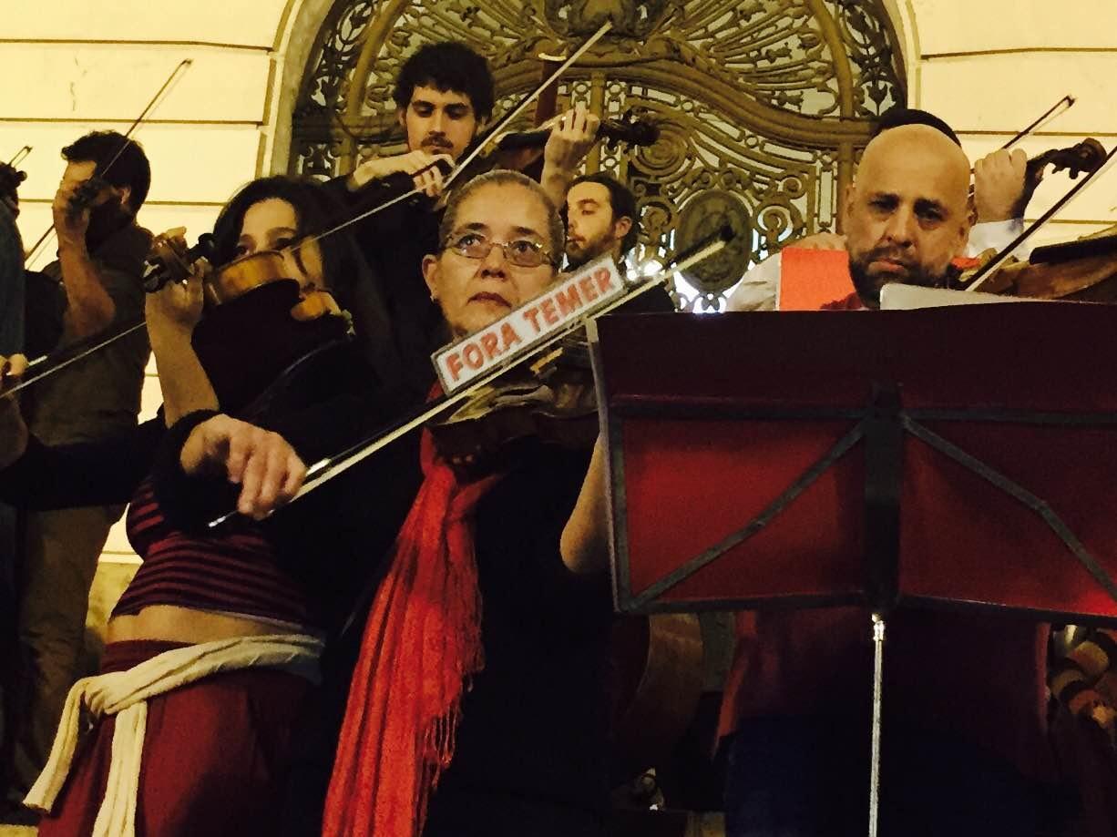 Uma violonista toca com um adesivo de 'Fora Temer' grudado no arco de seu instrumento e chama a atenção dos fotógrafos