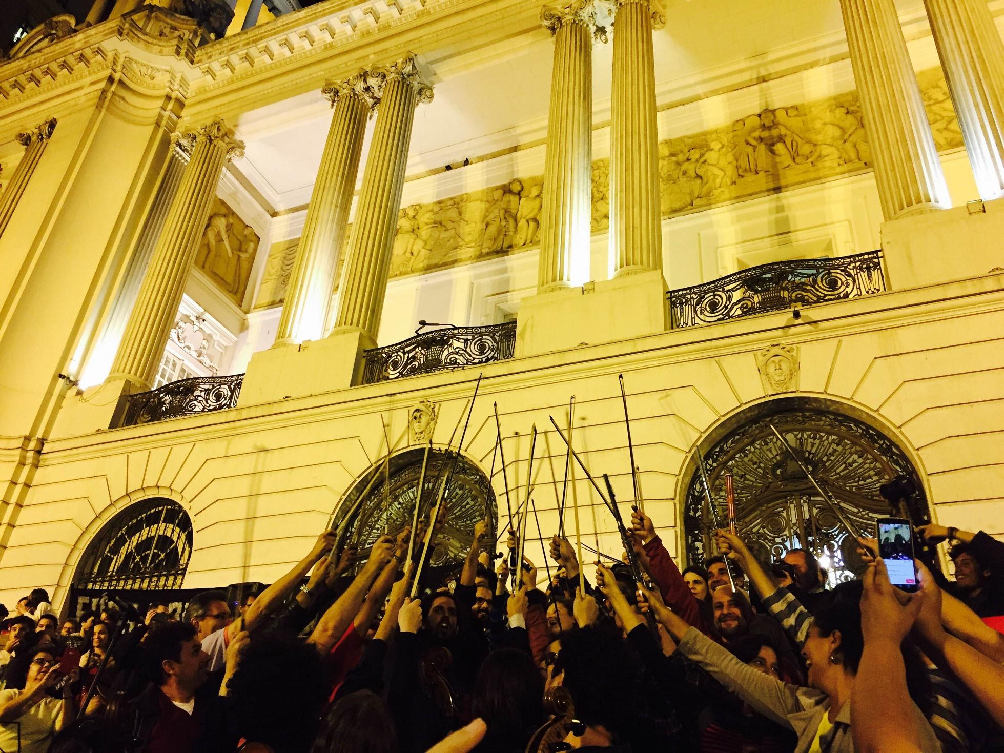 """Ao final de """"Carmina Burana"""" os músicos erguem os arcos dos instrumentos em sinal de protesto"""