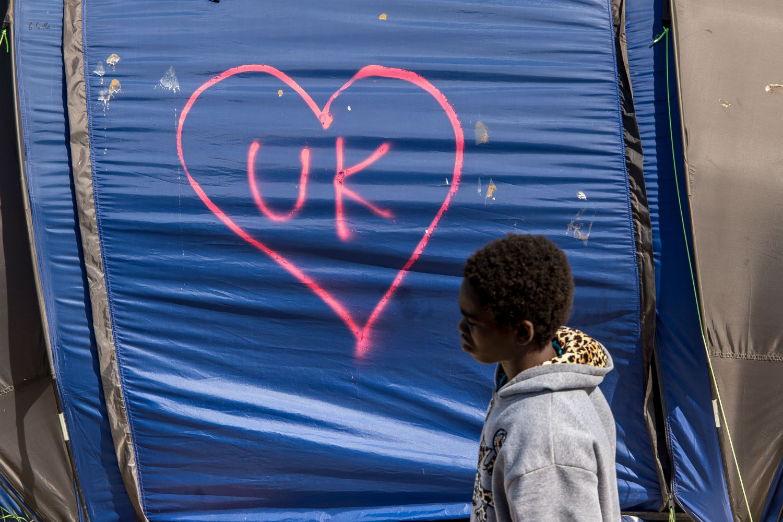 Menino passa por tenda em campo de refugiados de Calais