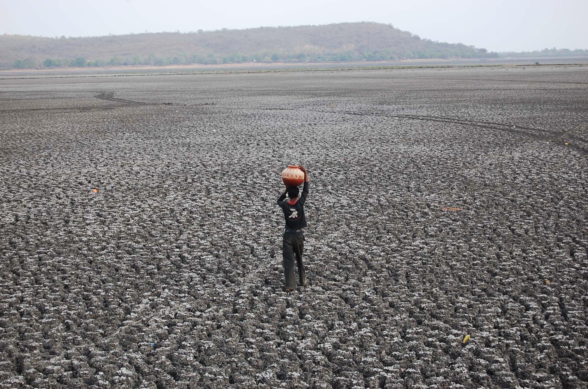 Homem caminha sobre o maior lago artifical da Ásia, o Upper Lake, em Bhopla, na Índia, está seco