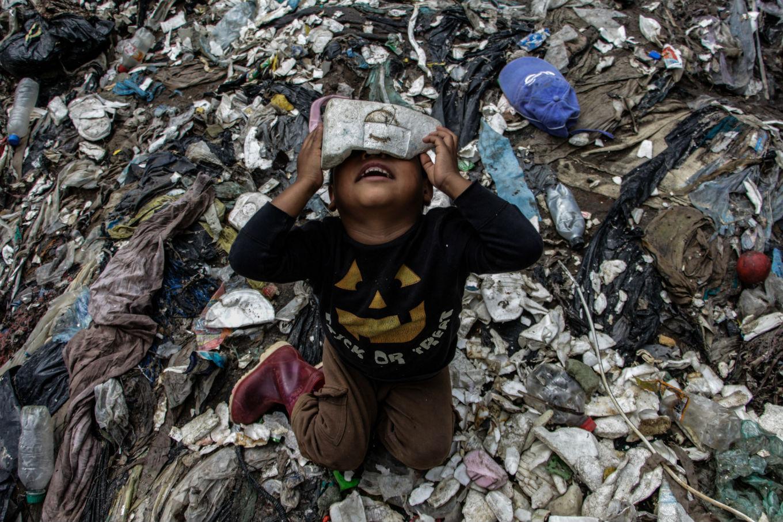 Menino brincando no lixo. Foto de Josue Decavele/ Anadolu Agency/ AFP