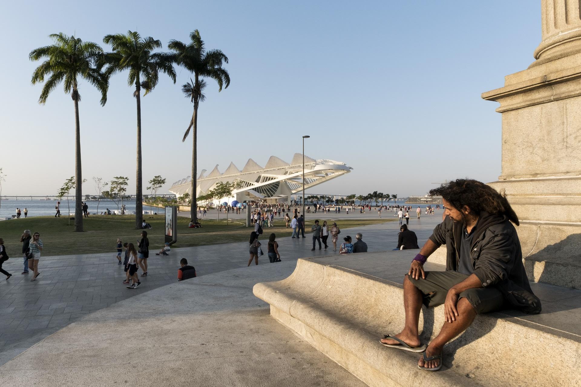 Um homem sentado num monumento observa as pessoas passeando em torno do Museu do Amanhã. Foto de Peter Bauza/DPA