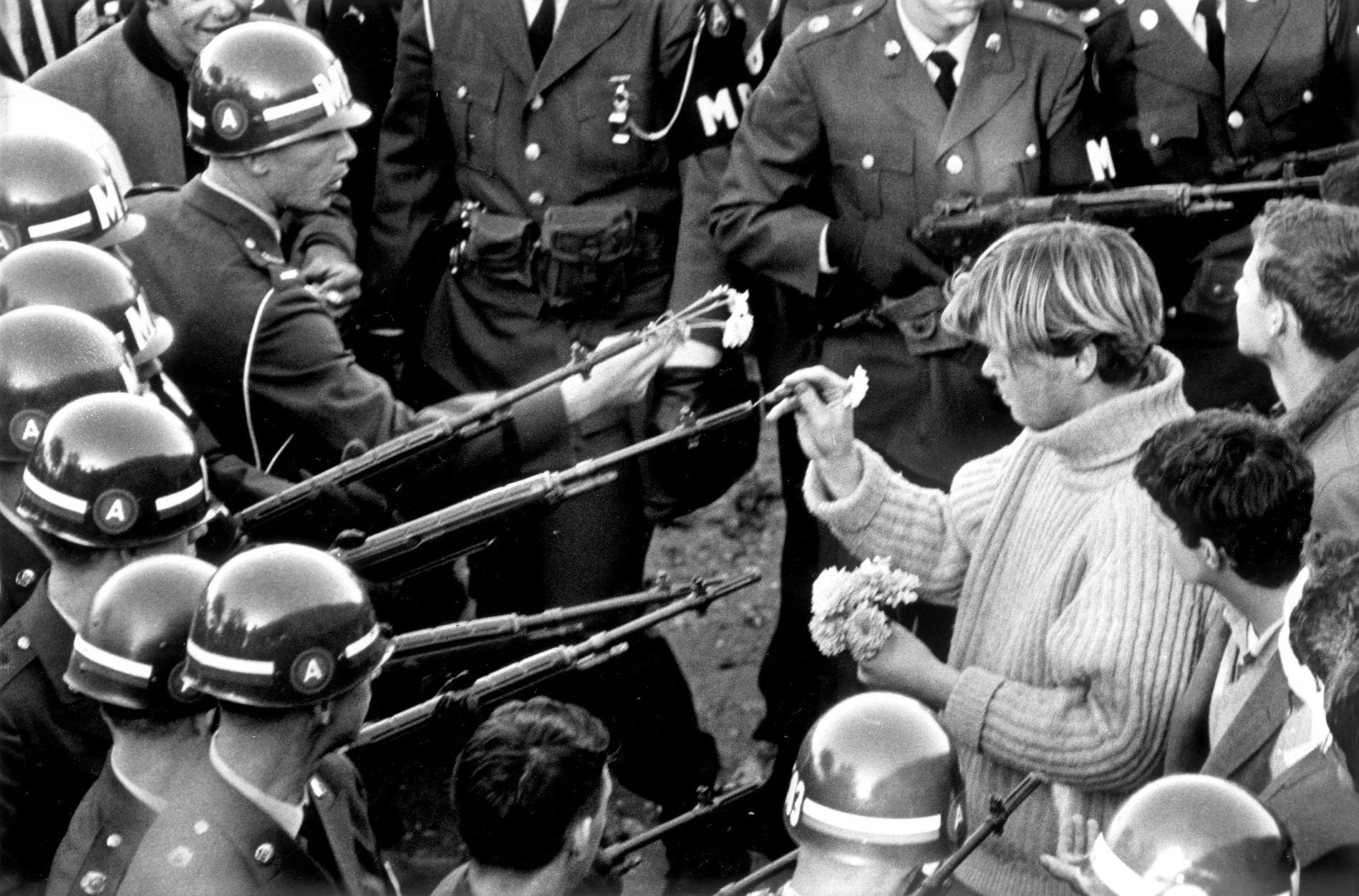 Em 1967, em frente ao Pentagono, nos EUA, um ativista põe flores no cano das armas. Foto de Bernie Boston/The Washington Post/via Getty Images
