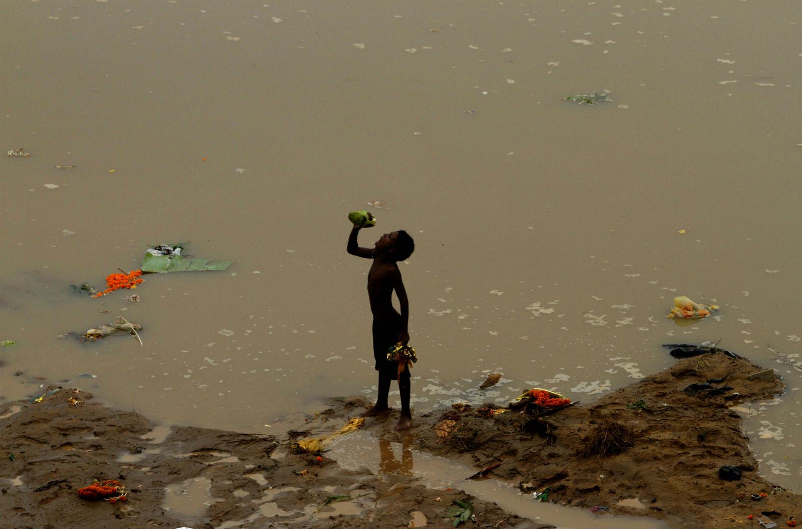 Menino bebendo resto de água de coco, kuakhai, na Índia. Foto de Biswaranjan Rout/NurPhoto/AFP
