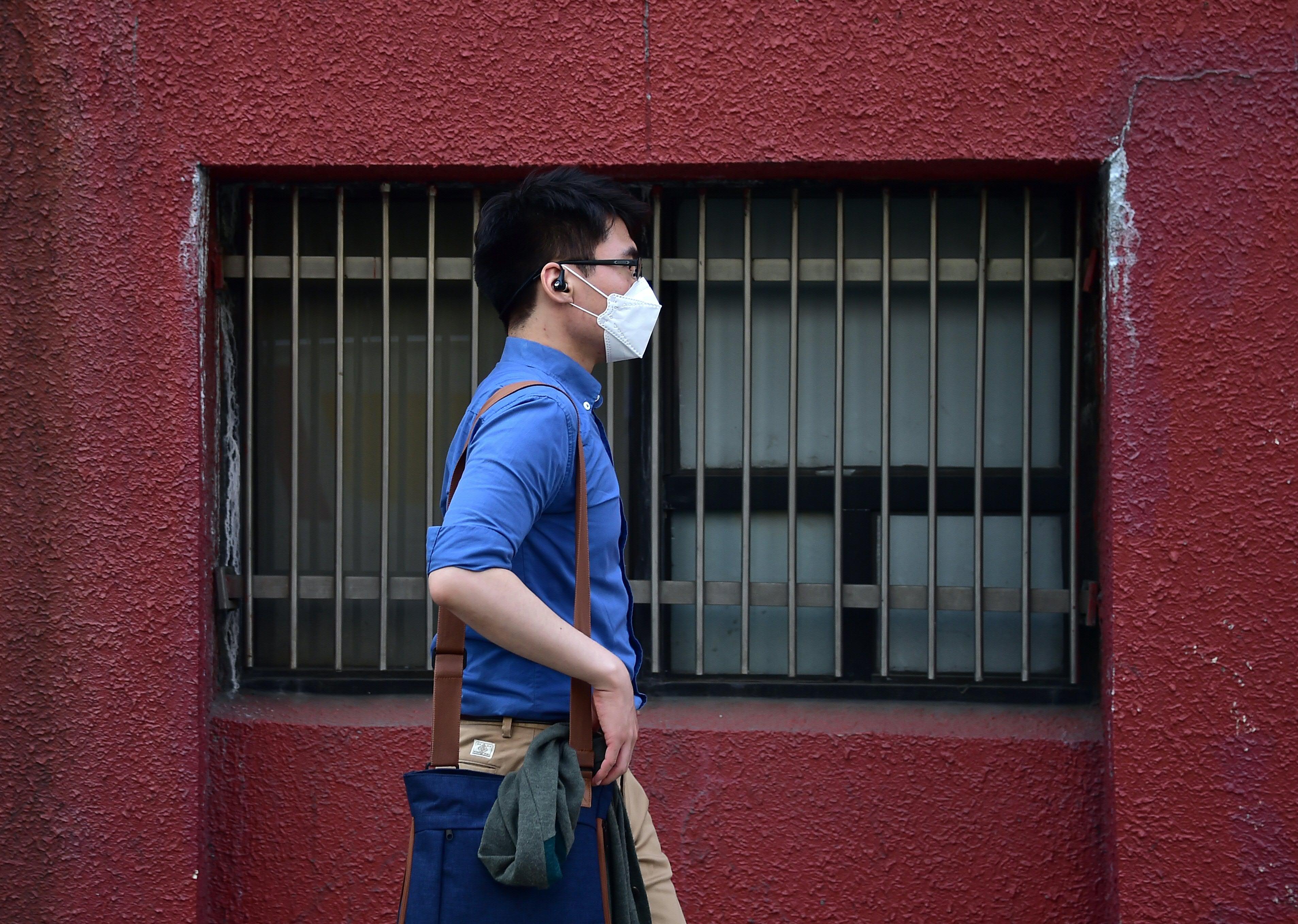 Homem com máscara andando pela rua de Seul, na Coreia do Sul