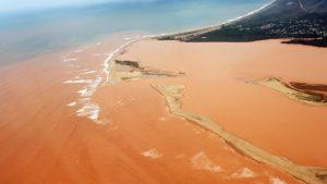 O Rio Doce com as águas vermelhas do minério de ferro já no território do Espírito Santo, em novembro passado (AFP/Estado do Espírito Santo/Fred Loureiro)