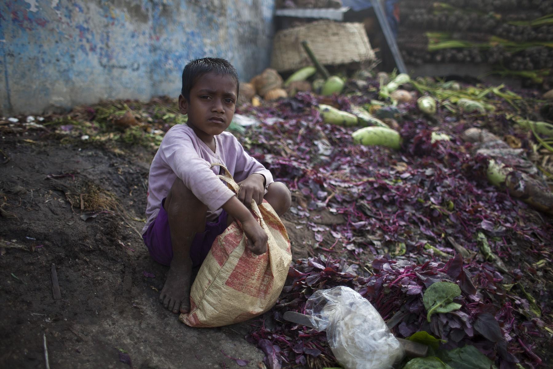 Menino recolhe vegetais num lixão em Bangladesh. Foto de Zakir Hossain Chowdhury/NurPhoto