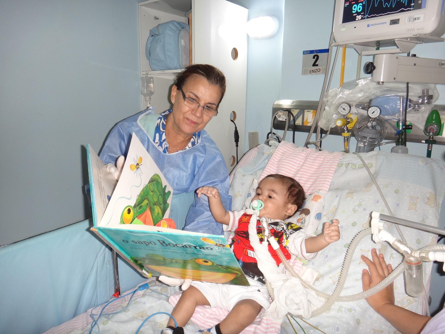 Voluntária mostra as figuras do livro para o bebê internado. Foto Divulgação