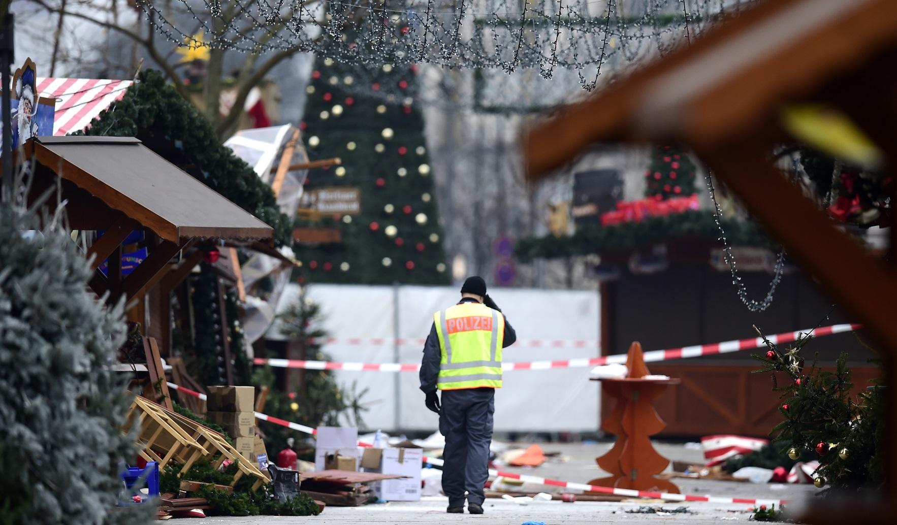 Policial caminha pelo mercado de Natal onde um atentado deixou 12 mortos e 48 feridos. Foto de Tobias Schwarz/AFP