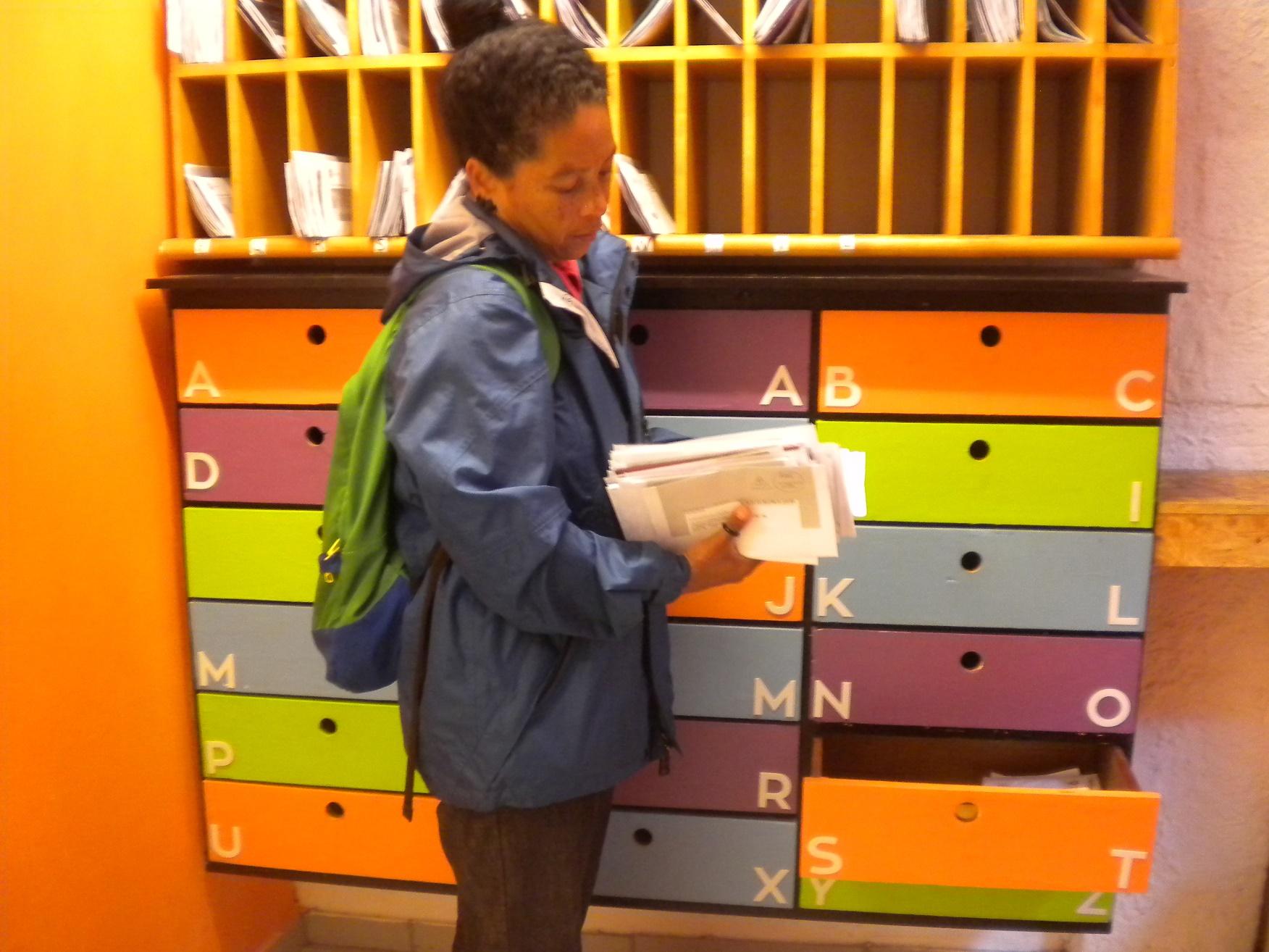 O serviço de entrega de correspondências dos moradores com gavetas coloridas organizadas por ordem alfabética. Foto de Elizabeth Oliveira