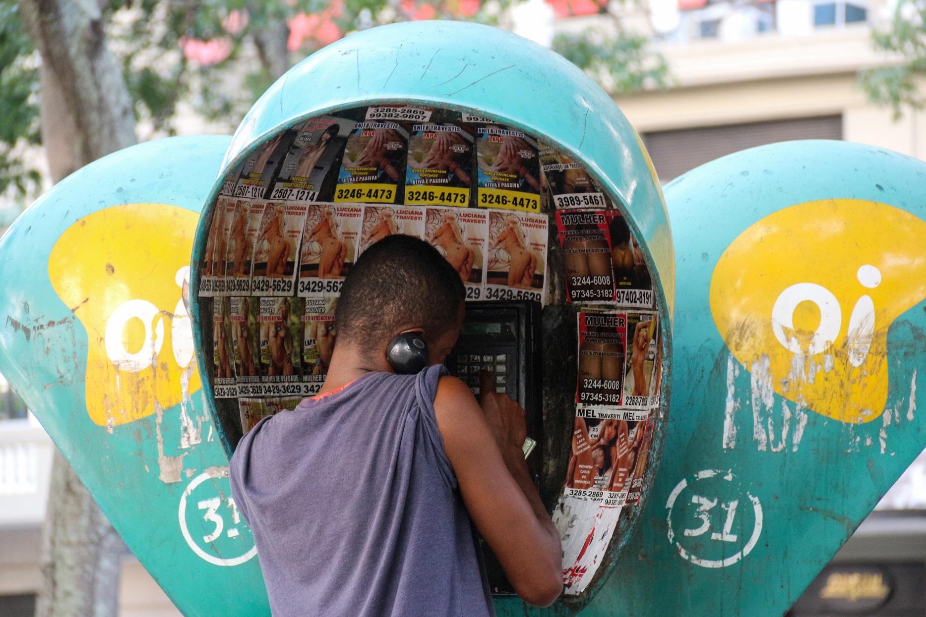 O raro usuário usa um dos muitos orelhões do Centro do Rio, lotado de anúncios de serviço de sexo. Foto de Luiz Souza/NurPhoto