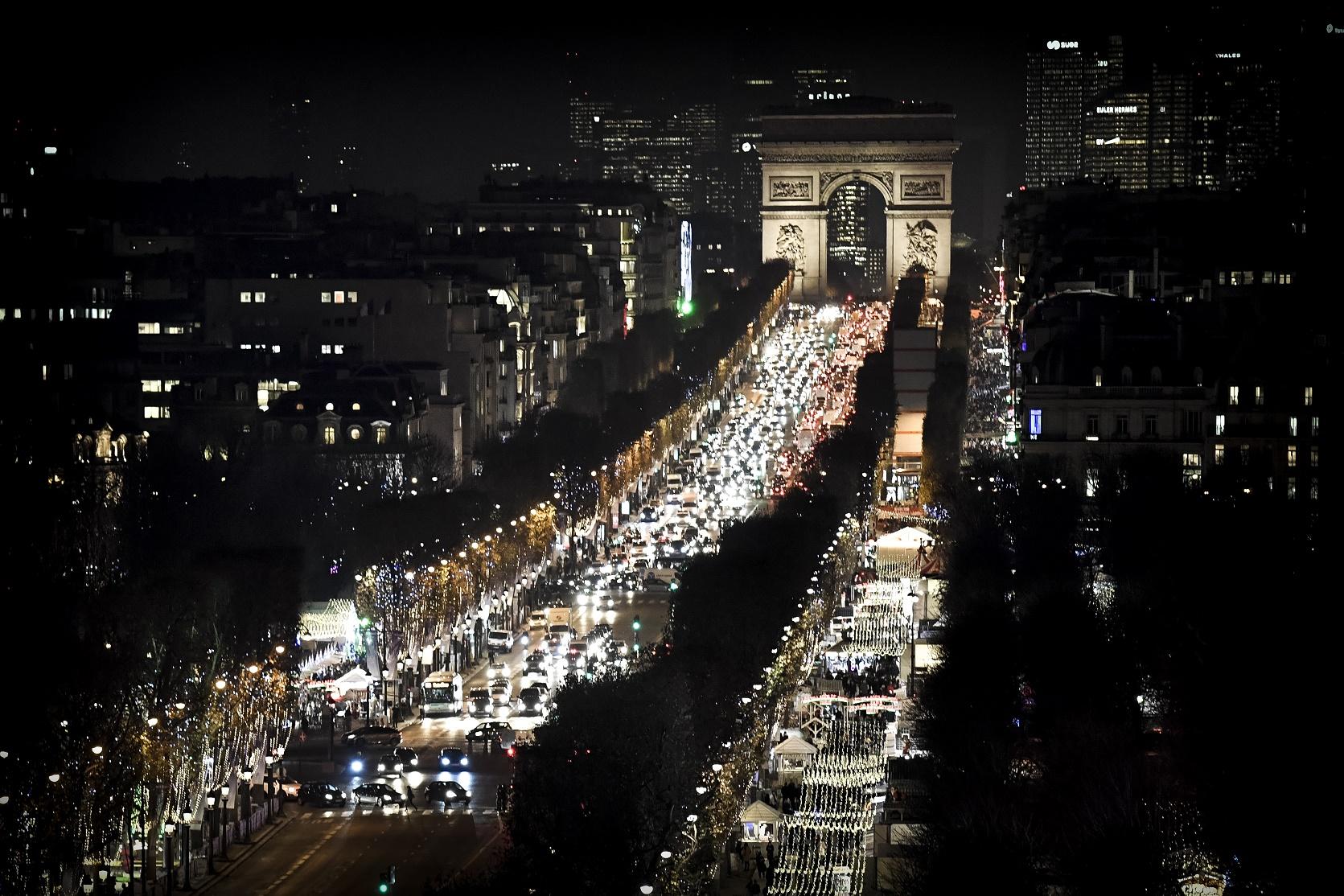 Imagem noturna do trânsito intenso na tradicional Champs Elysees, em Paris. Foto de Philippe Lopez/AFP