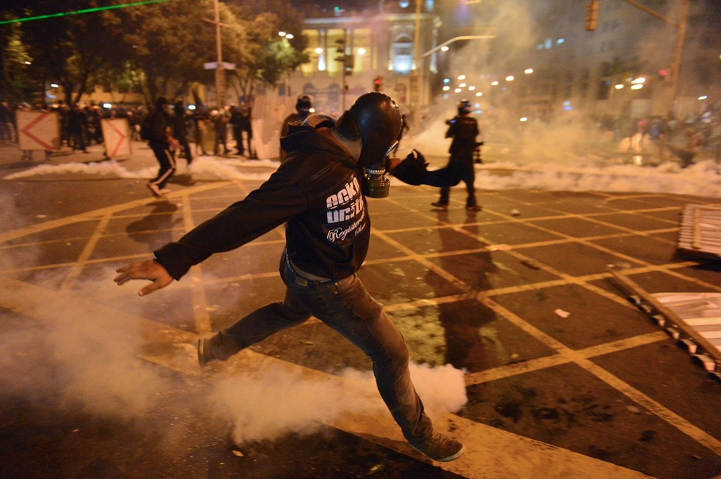 Manifestante com máscara de proteção em ação nos protestos de 2013. Foto: AFP/ Christophe Simon