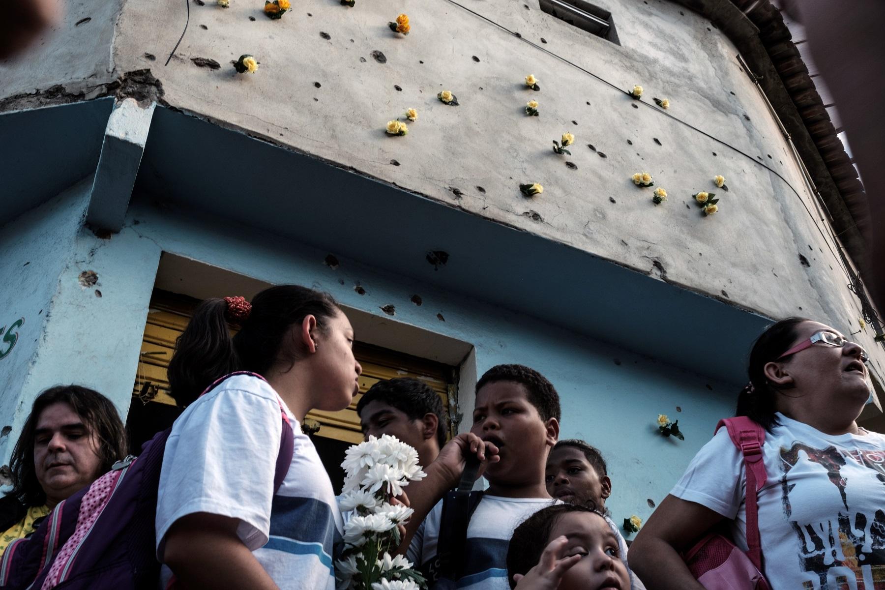 Crianças das escolas públicas da região põem flores nos buracos de bala das paredes. Foto Yasuyoshi Chiba/AFP