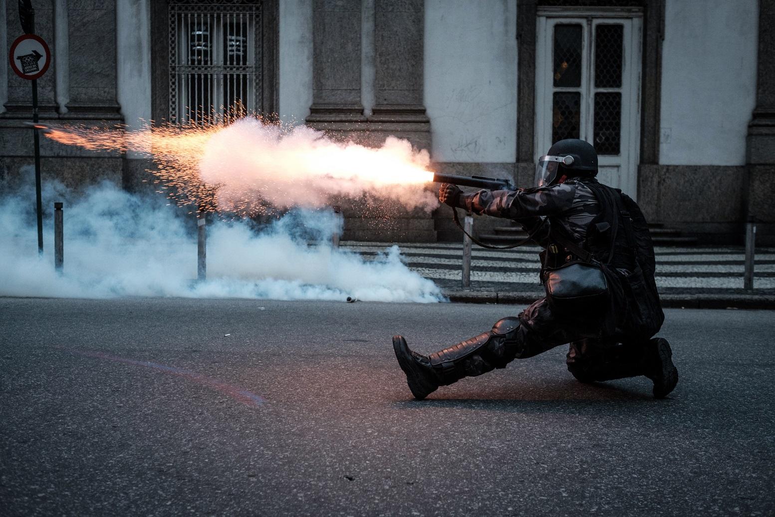 Policial dispara uma bomba de gás durante manifestação no Centro do Rio. Foto Yasuyoshi Chiba/AFP