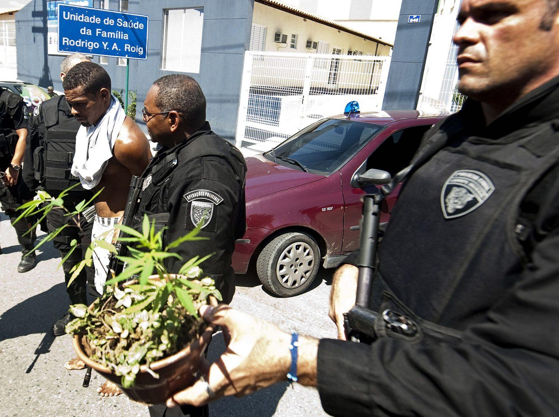 Policiais apreendem um vaso de maconha no morro do Alemão. Foto Antonio Scorza/AFP