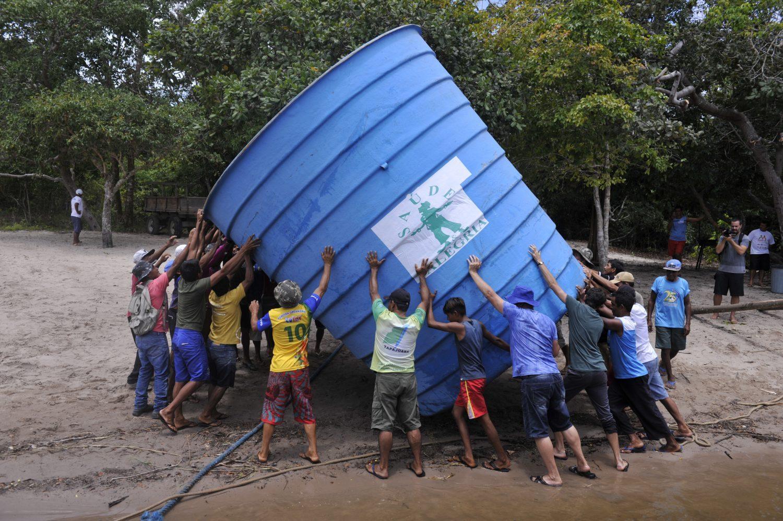 Ribeirinhos da comunidade de Anumã, no Tapajós, carregam caixa d'agua comunitária (Foto Chico Ferreira/Divulgação)
