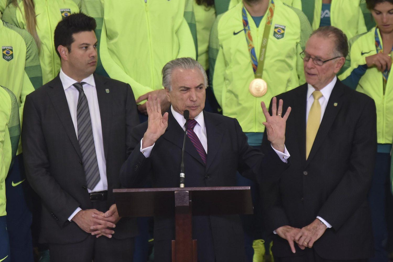 O presidente do COB, Carlos Arthur Nuzman, ao lado de Michel Temer, recebe os medalhistas olímpicos. Foto Ricardo Botelho/AFP