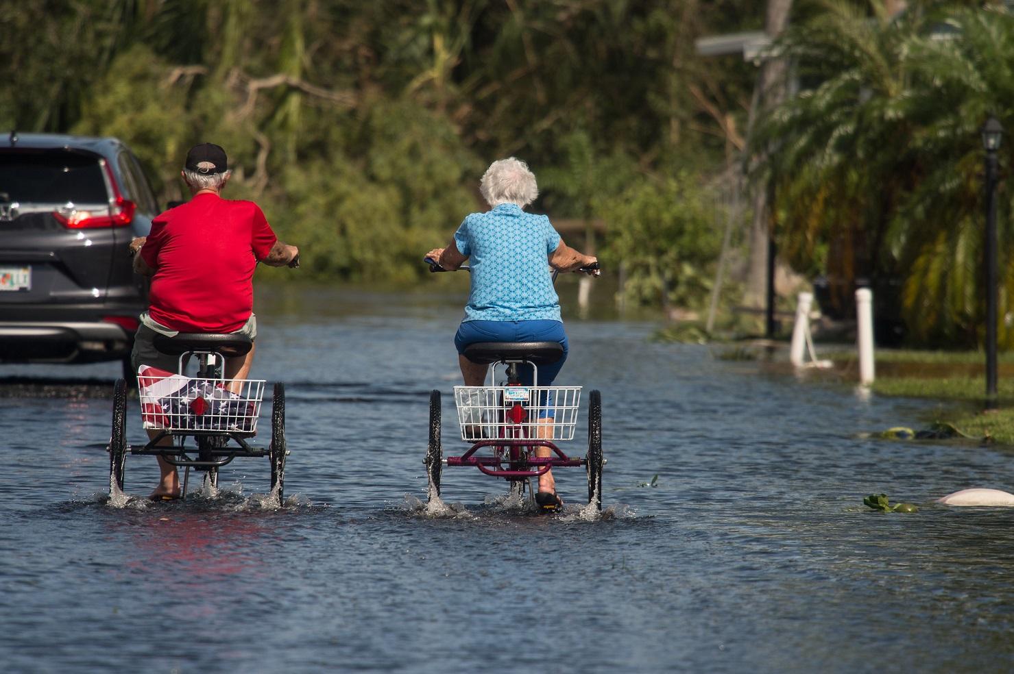 Casal pedala pelas ruas cheias de água da Flórida. Foto Nicholas Kamm/AFP