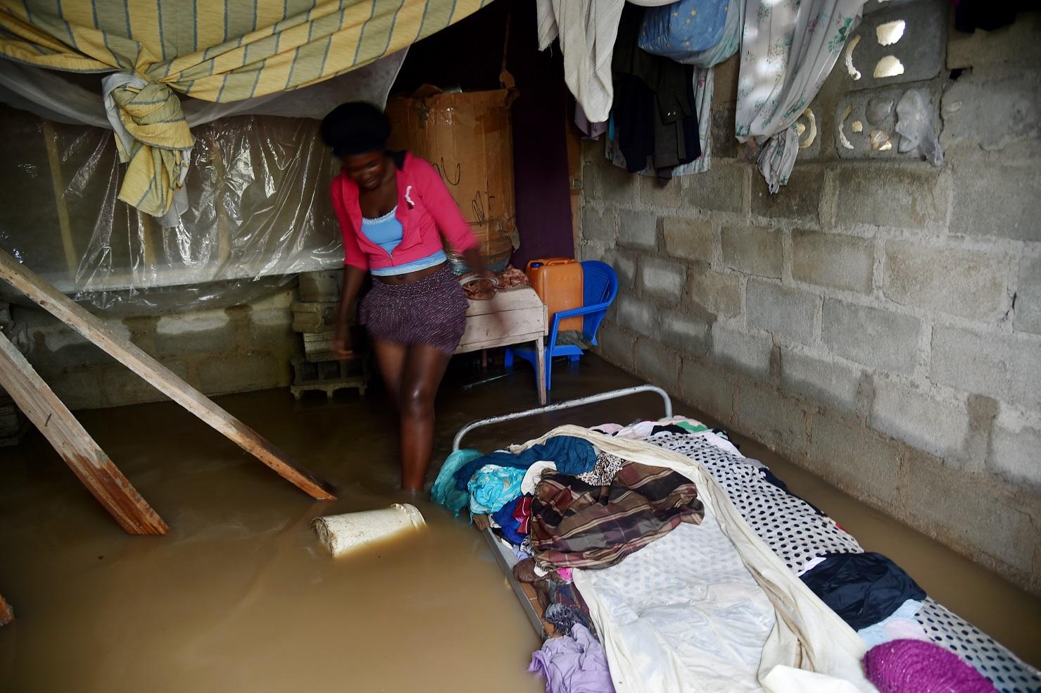 Marie Charlotte caminha dentro da sua casa, no Haiti, inundada pelo furacão Irma. Foto Hector Retamal/AFP