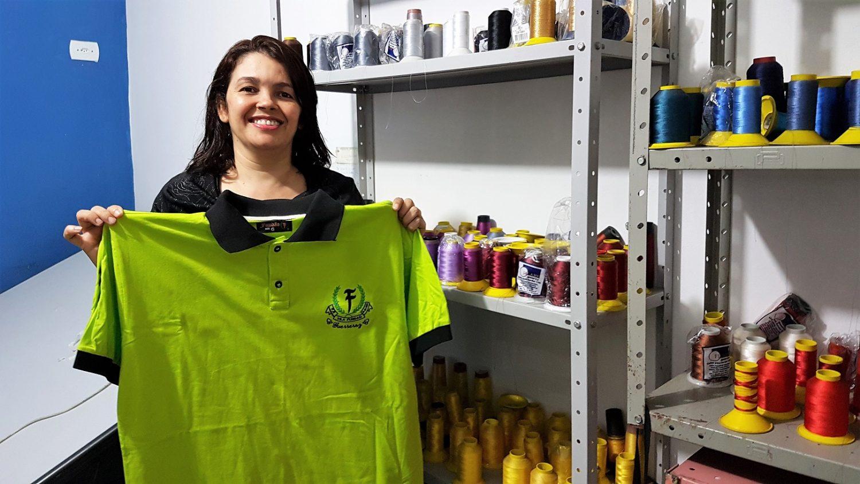 Maria da Consolação exibe, feliz, uma das camisas produzidas para as grifes do Capão Redondo. Foto Florência Costa