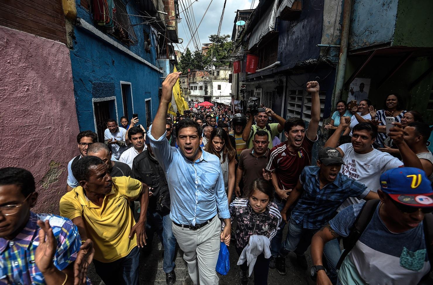 O candidato de oposição ao governo Carlos Ocariz (C) faz campanha no Centro de Caracas. Foto Juan Barreto/AFP