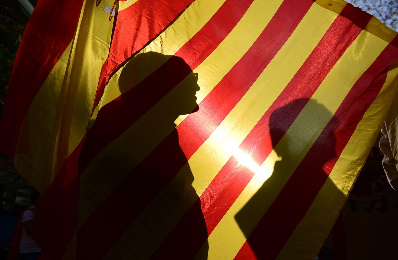 A sombra dos manifestantes na bandeira da conturbada Catalunha. Foto Pierre-Philippe Marcou/AFP