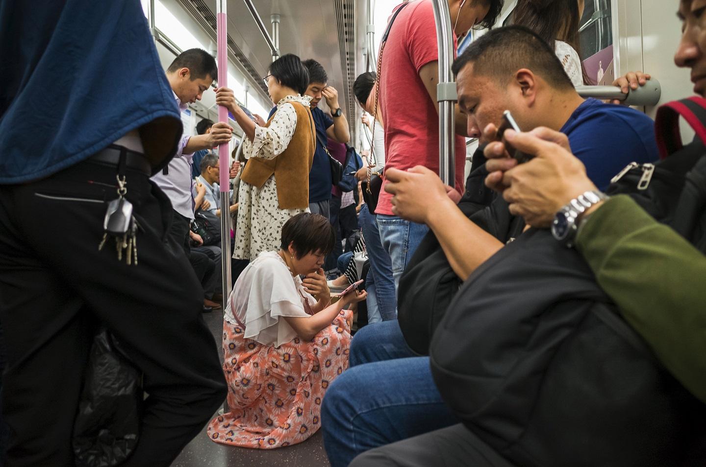 Chineses no metrô de Pequim com os seus smartphones. Foto An Weijun / Imaginechina