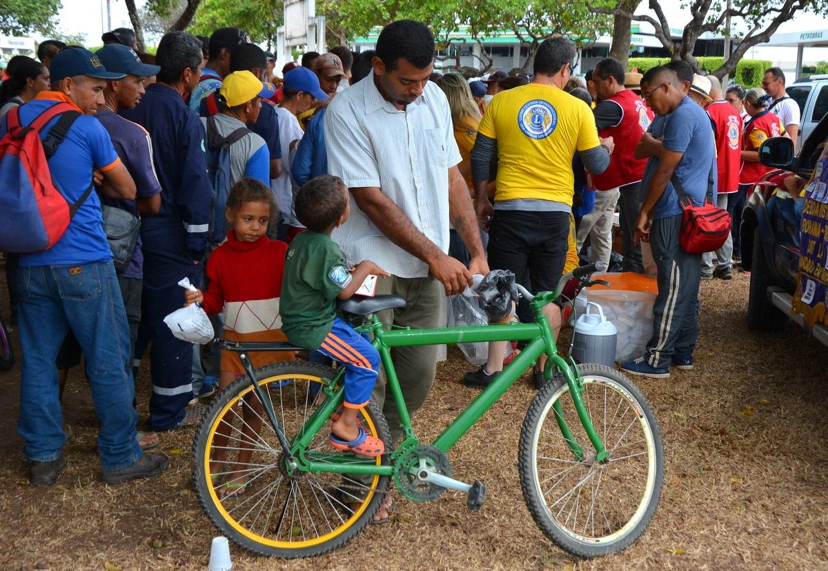 Luiz Mota, 33 anos, garantiu um litro de leite e pães para os dois filhos. Ele carrega as crianças numa bicicleta emprestada. Foto Charles Wellington