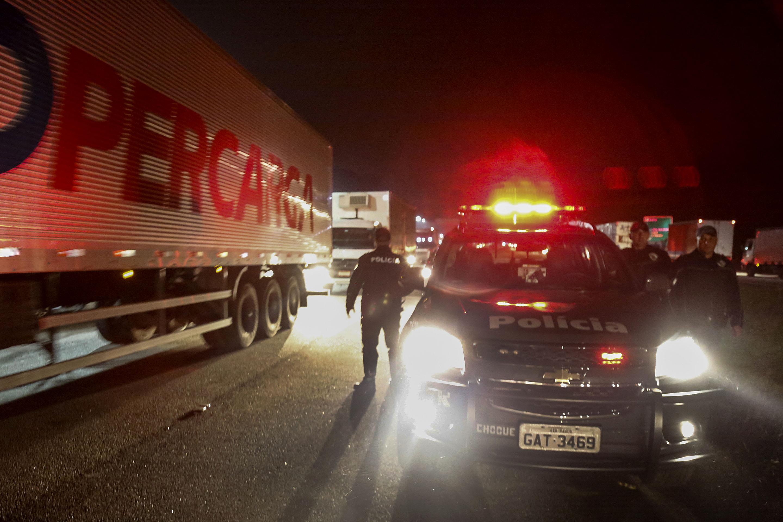 A polícia tenta organizar o fluxo de veículos no Rodoanel, em São Bernardo do Campo: o Brasil paralisado. (Foto Miguel Schincario/ AFP)