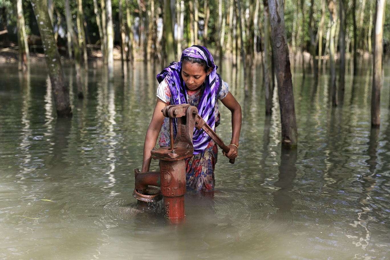 Em Bangladesh, a jovem Salma coleta água para abastecer a família. As doenças de veiculação hídrica estão entre as principais causas de mortalidade infantil. Foto Mushfiqul Alam/NurPhoto