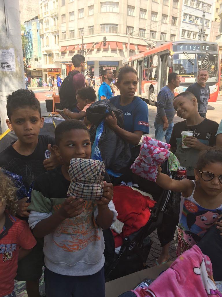 Crianças recebem os sacos de dormir feitos com os tecidos dos guarda-chuvas. Foto Divulgação