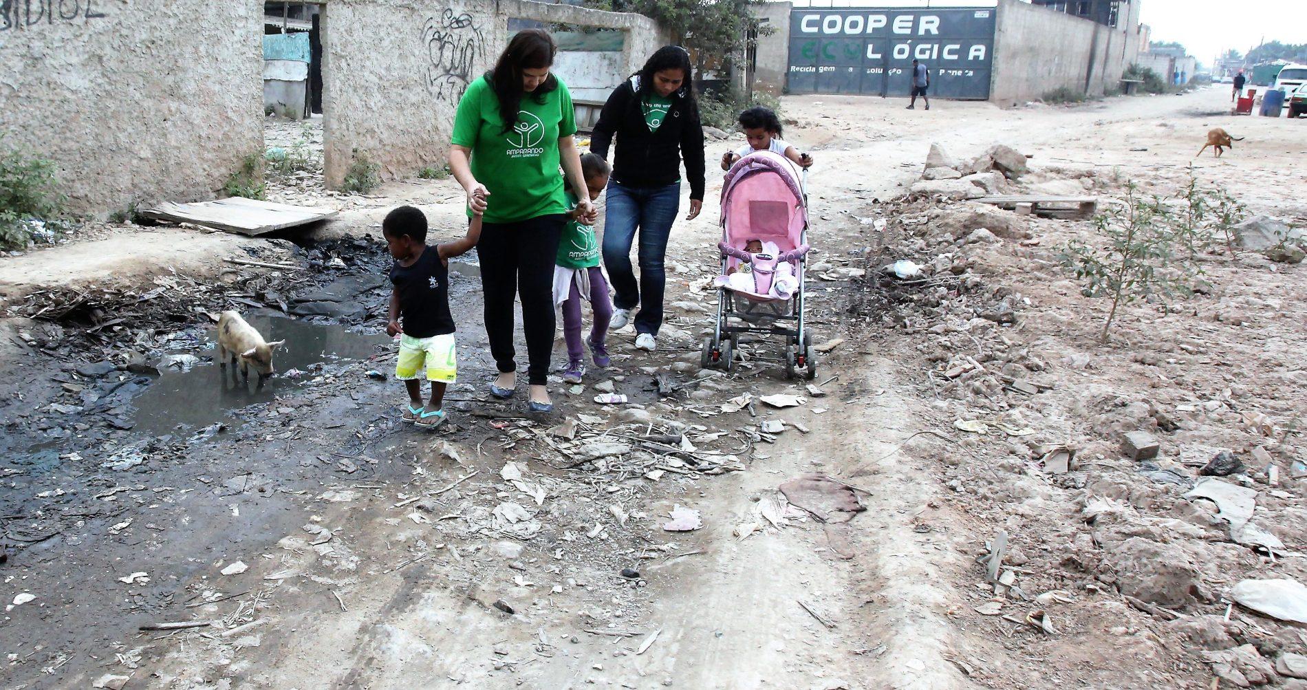 Roberta (de verde) e uma parceira da Amparanda Jardim Gramacho, com crianças atendidas pela ONG: entre lixo e porcos. Foto: Severino Silva/Divulgação