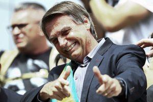 O candidato Jair Bolsonaro simula duas armas com as mãos. Gesto marcou a sua campanha. Foto Heuleer Andrey/AFP
