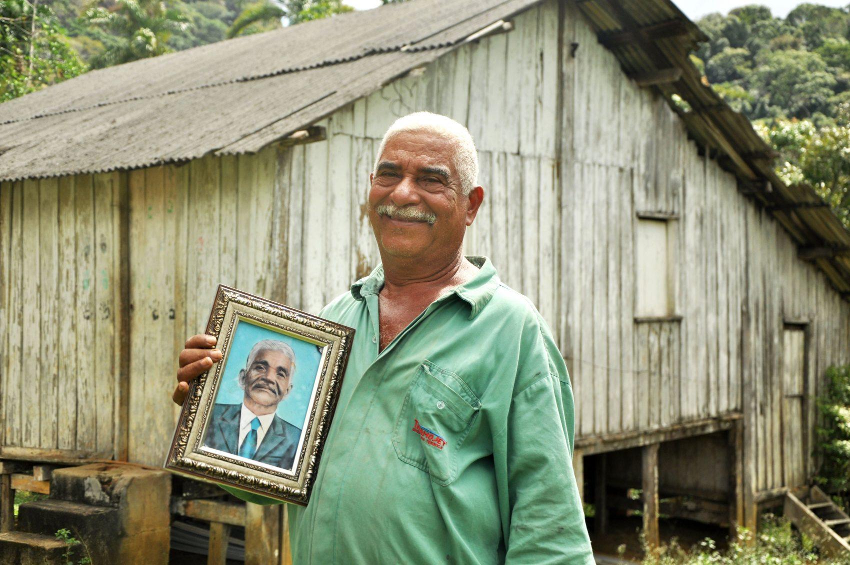 Seu Lírio (Rosemiro Ferreira da Silva), pajé da Serra do Padeiro, com o retrato de seu pai, João de Nô (Foto: Daniela Alarcon/divulgação)