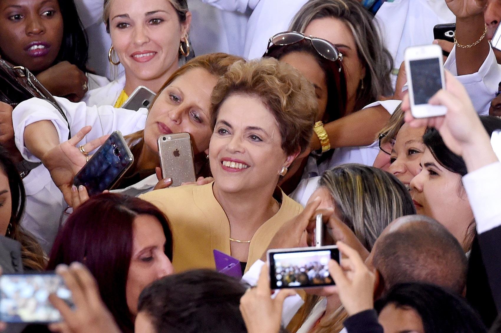 A então presidente Dilma Rousseff posa com médicas cubanas depois de uma cerimônia de extensão do programa Mais Médicos em Brasilia, em 2016 (Foto: EVARISTO SA / AFP)