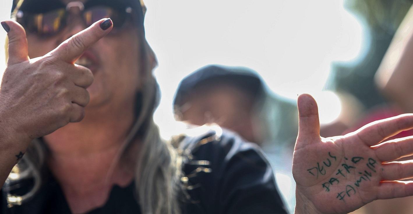 Simpatizante de Bolsonaro faz o gesto da arma com a mão e exibe as palavras Deus, Pátria e Família. Foto Miguel Schincariol