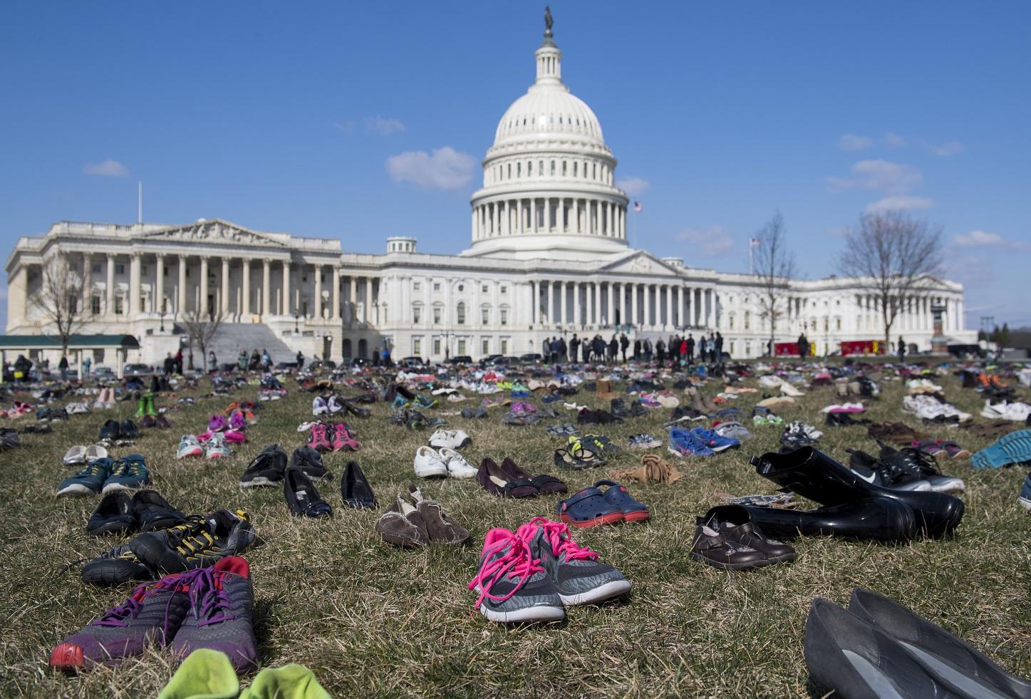 Em um protesto em frente ao Capitólio, em Washington, sete mil pares de calçados lembram as crianças mortas por arma de fogo no país. Foto Saul Loeb/AFP