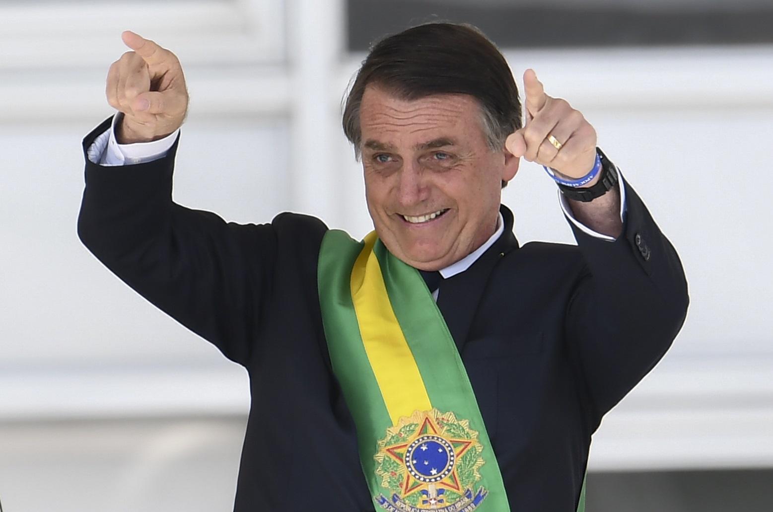 Jair Bolsonaro acena para o público após receber a faixa presidencial. Foto Evaristo Sá/AFP