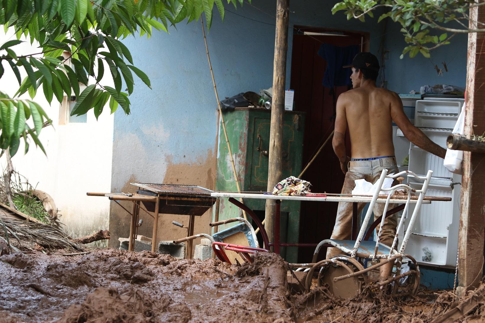 Uma das vítimas do desastre tenta salvar uma geladeira no meio dos escombros. Foto Doug Patrício/DPA