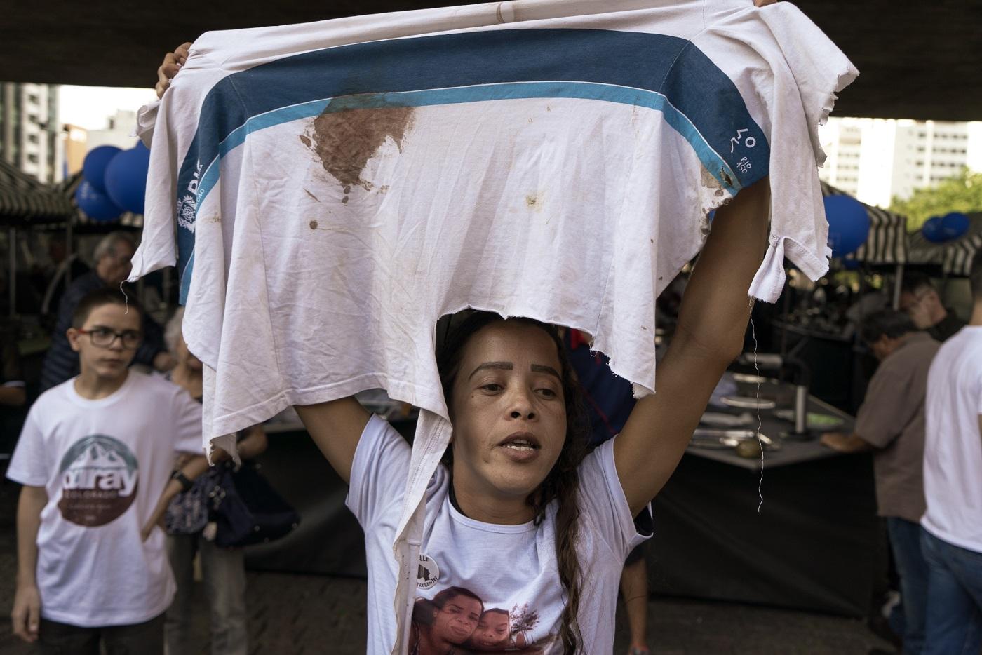 Bruna Silva segura a camisa da escola que seu filho Marcus Vinícius usava no dia em que foi morto. Foto: Daniel Arroyo