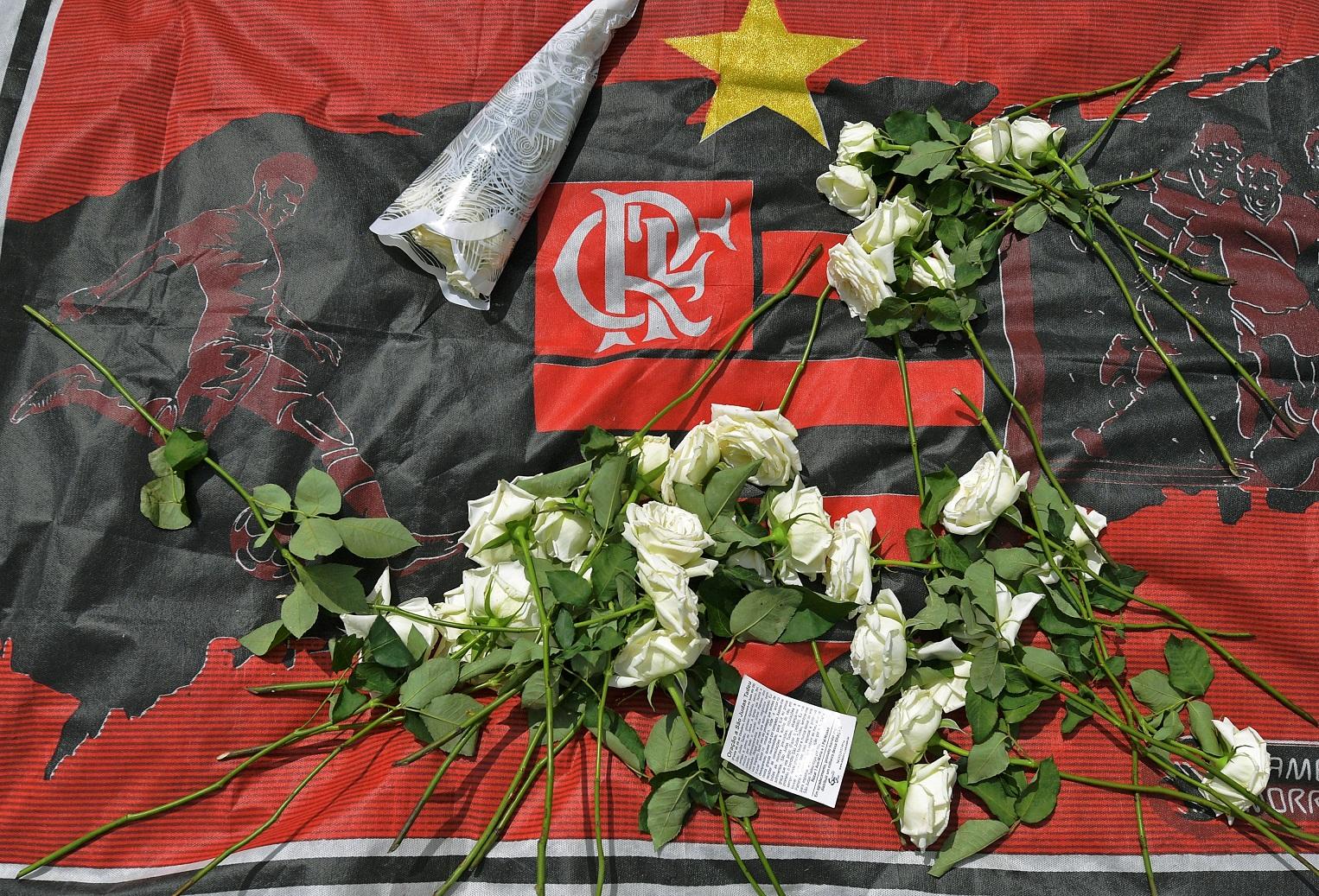 Flores sobre a bandeira do Flamengo. Luto pela tragédia que matou dez pessoas. Foto Carl de Souza/AFP