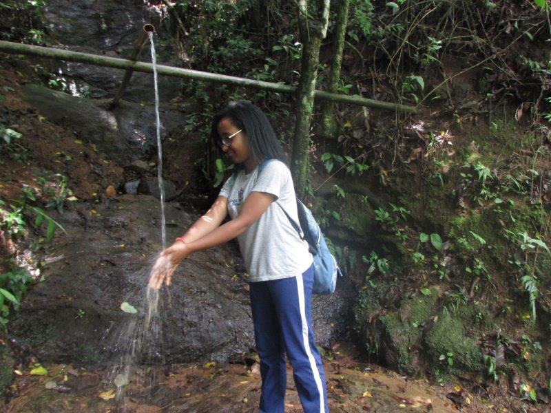 Aluna com água da fonte na fazenda do projeto: conscientização sobre os riscos para a água do planeta (Foto Divulgação)